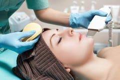 L'estetista fa la pulizia ultrasonica del fronte cosmetology Immagini Stock