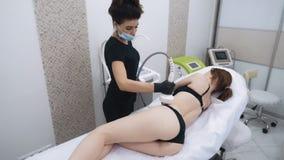 L'estetista fa la terapia di sollevamento sulla donna che il corpo utilizza il dispositivo di contorno, movimento lento video d archivio