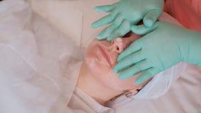 L'estetista in guanti sfrega il fronte della ragazza crema nel primo piano del salone di bellezza Trattamenti di massaggio nel sa fotografie stock libere da diritti