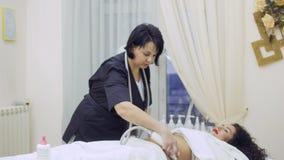 L'estetista massaggia lo stomaco del ` s della donna con l'apparecchiatura di GPL video d archivio