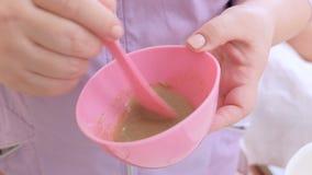 L'estetista mescola gli ingredienti per una maschera dell'alginato delle alghe o della frutta Manicotto in gomma rosa con la biom archivi video