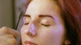 L'estetista pettina le sopracciglia del cliente dopo la verniciatura con una spazzola stock footage