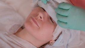 L'estetista rimuove la maschera dell'alginato dal fronte di una donna Bella ragazza sulla procedura nel salone di bellezza Cosmet