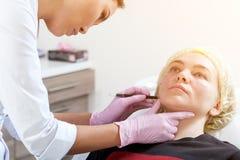L'estetista spinge una siringa per iniettare Botox fotografia stock
