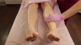 L'esthéticien applique une crème hydratante aux jambes de la fille après un dépilage de sucre banque de vidéos