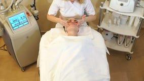 L'esthéticien font un massage facial avec de la crème de hydrater à une jeune fille banque de vidéos