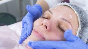 L'esthéticien met la crème sur le visage de la femme Traitement facial de Cosmetologist Plan rapproché banque de vidéos