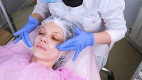 L'esthéticien met le masque sur le visage de la femme Visage de nettoyage banque de vidéos
