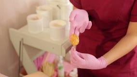L'esthéticien prend la pâte de sucre des banques pour le dépilage des aisselles de femme banque de vidéos