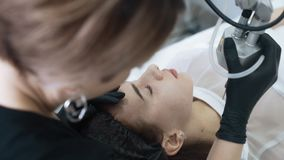 L'esth?ticien de mouvement lent fait l'?pluchage facial de laser pour la femme avec le dispositif sp?cial clips vidéos