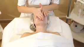 L'esth?ticien font un massage facial avec de la cr?me de hydrater ? une jeune fille banque de vidéos