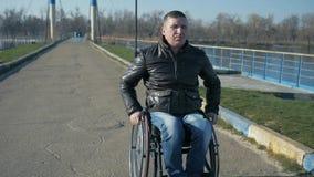 L'estropié monte à sur le pont près de la rivière sur le fauteuil roulant, mâle de portrait dessus banque de vidéos
