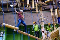 L'età 6-12 dei bambini assiste al parco rampicante di avventura dell'interno Immagini Stock
