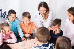 L'età elementare ha interessato i bambini alla tavola con il gioco da tavolo e Fotografie Stock