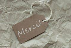 L'etichetta beige con i mezzi di Merci del francese vi ringrazia fondo di carta fotografia stock