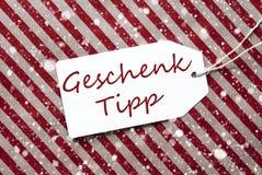 L'etichetta, carta da imballaggio rossa, Geschenk Tipp significa la punta del regalo, fiocchi di neve Fotografie Stock Libere da Diritti
