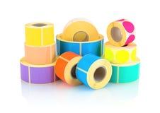 L'etichetta colorata rotola su fondo bianco con la riflessione dell'ombra Bobine di colore delle etichette per le stampanti Fotografia Stock
