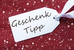 L'etichetta su fondo rosso, fiocchi di neve, Geschenk Tipp significa la punta del regalo Immagine Stock