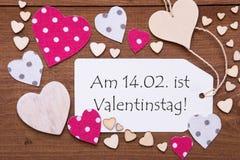 L'etichetta, testo Valentinstag significa il giorno di biglietti di S. Valentino, cuori rosa Immagine Stock