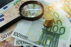 L'euro billet de banque et pièces de monnaie avec la loupe et le soleil évasent comme f Images libres de droits
