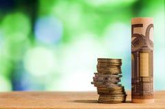 L'euro cinquanta ha rotolato la banconota della fattura, con le euro monete su blurre verde Fotografia Stock