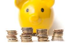 L'euro conia i mucchi sul porcellino salvadanaio giallo su backgr bianco Immagini Stock