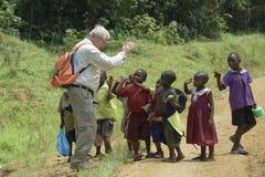 L'europeo bianco accoglie favorevolmente i bambini africani Immagini Stock