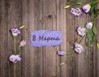 L'Eustoma fleurit autour de la carte de papier pourpre de métier avec le 8 mars dessus Photos libres de droits