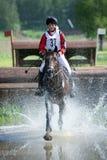 L'eventer de femme sur le cheval est couru dans le saut d'eau photographie stock