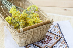 L'everlast nain fleurit le bouquet dans un panier en osier et la serviette avec la broderie sur la table en bois légère Photo libre de droits