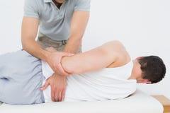 L'examen masculin de physiothérapeute équipe de retour Photo libre de droits
