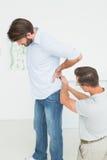 L'examen masculin de physiothérapeute équipe de retour Photo stock
