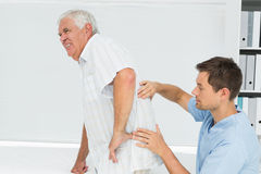 L'examen masculin de physiothérapeute supérieur équipe de retour Photographie stock