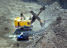 L'excavatrice énorme et un camion sur le granit extraient image libre de droits