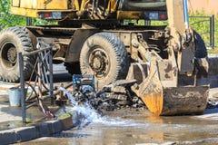 L'excavatrice aide à éliminer le problème de casser un tuyau dans la rue un jour chaud d'été Photos libres de droits