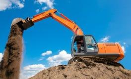 L'excavatrice avec le métal suit décharger la saleté au chantier de construction Image libre de droits