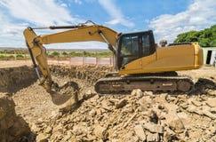 L'excavatrice, bêcheur dégage la terre pour la construction de logements Photos stock