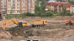 L'excavatrice charge l'argile utilisant le seau dans le camion à benne basculante clips vidéos