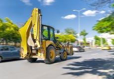 L'excavatrice conduit ou va rapidement sur la rue avec la circulation dense avec le ciel bleu et les arbres verts à l'arrière-pla image stock