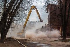 L'excavatrice démolit le vieux bâtiment scolaire Image libre de droits