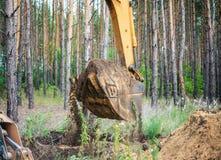 L'excavatrice effectue le travail d'excavation en creusant la terre avec un seau photographie stock