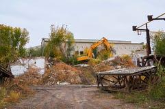 L'excavatrice jaune casse un vieil immeuble de brique image libre de droits