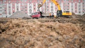 L'excavatrice jaune charge l'argile utilisant son grand seau banque de vidéos