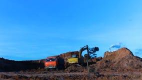 L'excavatrice jaune Digs Ground et met dans le verseur clips vidéos