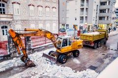 L'excavatrice nettoie les rues d'un grand nombre de neige Photos stock