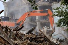 L'excavatrice ratissent le bâtiment tombé, débris est rassemblée par le seau images stock