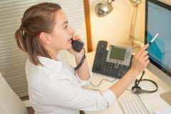 L'expéditeur de fille travaille avec le téléphone Au centre d'appels photographie stock libre de droits