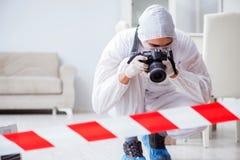 L'expert médico-légal à la scène du crime faisant l'enquête photo stock