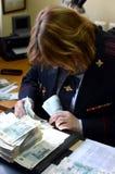 L'expert médico-légal du centre légal de la police entreprend une étude des billets de banque pour l'authenticité photos stock