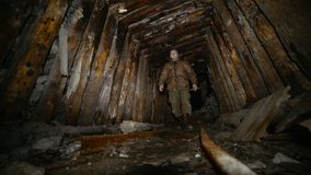 L'explorateur avec une lampe-torche marche le long d'une vieille mine abandonnée avec des rails banque de vidéos